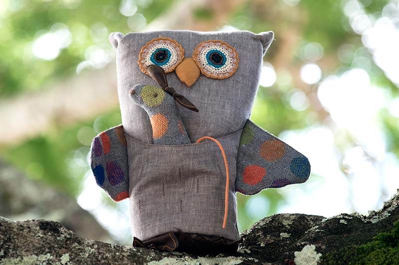 Maileg Owl stuffed toy sitting on a tree limb.