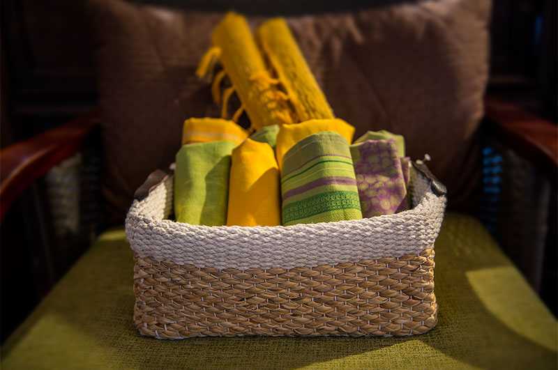 Picture of woven basket filled with rolled linens.