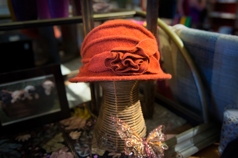 Beautiful orange, vintage-styled woman's hat on display at Kong Lung Trading