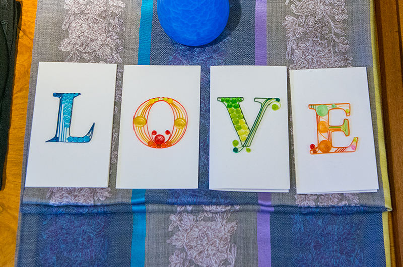 four greeting cards spell out LOVE