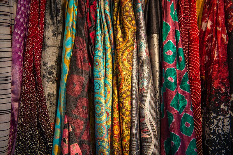 Lots of colorful, patterned scarves on display.