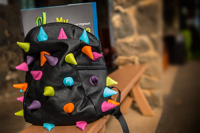 Bright colored spikes on a black backpack by Mad Pax.